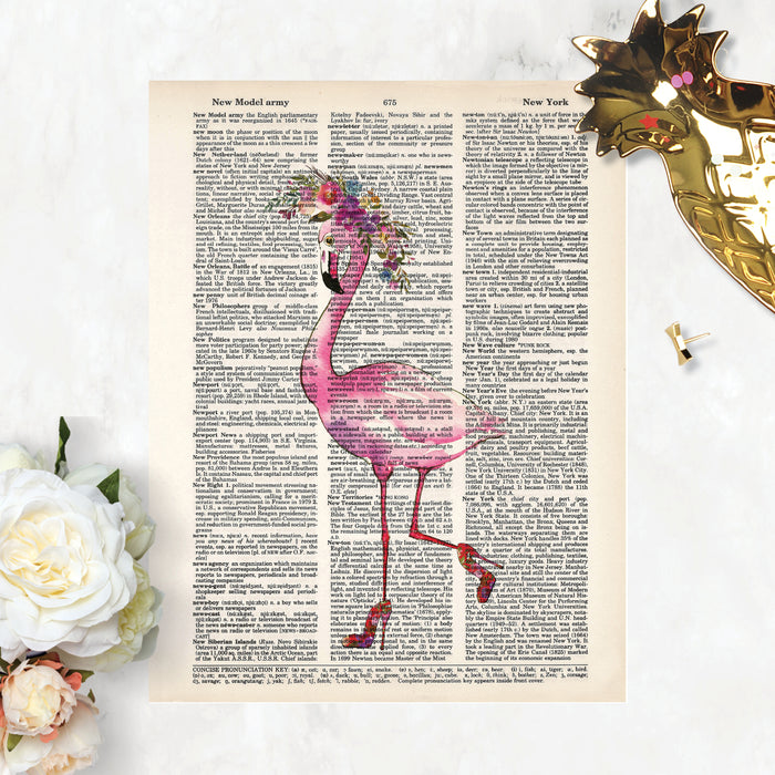 watercolor flamingo wearing a watercolor flower crown in shades of pink, purples, and blues she has high heels on her feet and one leg is kicked back printed on salvaged dictionary paper