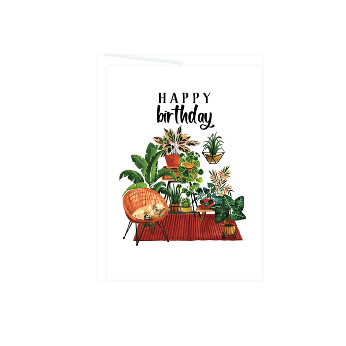 happy birthday in black ink above a plant scene of plants on plant stands anchored by a rust colored rug and a wicker chair with a tan puppy sleeping on it, greeting card is blank inside