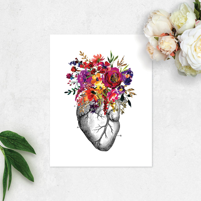 vintage etching of an anatomical heart topped with watercolor flowers in shades of pink, purple, yellow, and golden tones printed on matte white paper