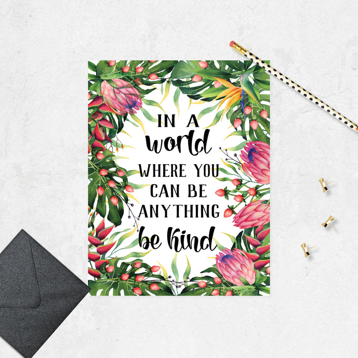 Tropical watercolor greenery and flowers surround the words In a world where you can be anything be kind on matte white paper