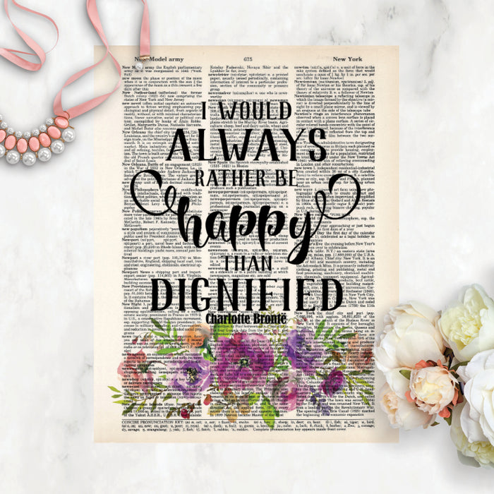 I would always rather be happy than dignified quote by Charlotte Bronte in black in above watercolor flowers in purple tones with greenery on salvaged dictionary page
