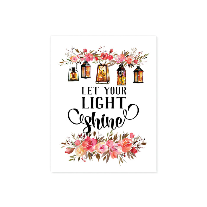 let your light shine is printed in black ink, at the top of the page there is a spray of pink and salmon colored flowers with five lanterns glowing amber with light, there are matching flowers and greenery at the bottom of the matte white paper