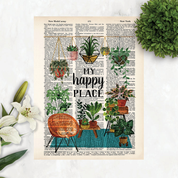 my happy place surrounded by haing plants and plants on a teal blue rug with plant stands and more plants, there is also a wicker chair with a yellow cat curled up sleeping printed on dictionary page