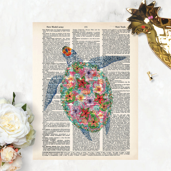 sea turtle in watercolors but with tropical flowers decorating the shell in shades of pink, purple, yellow printed on a dictionary page