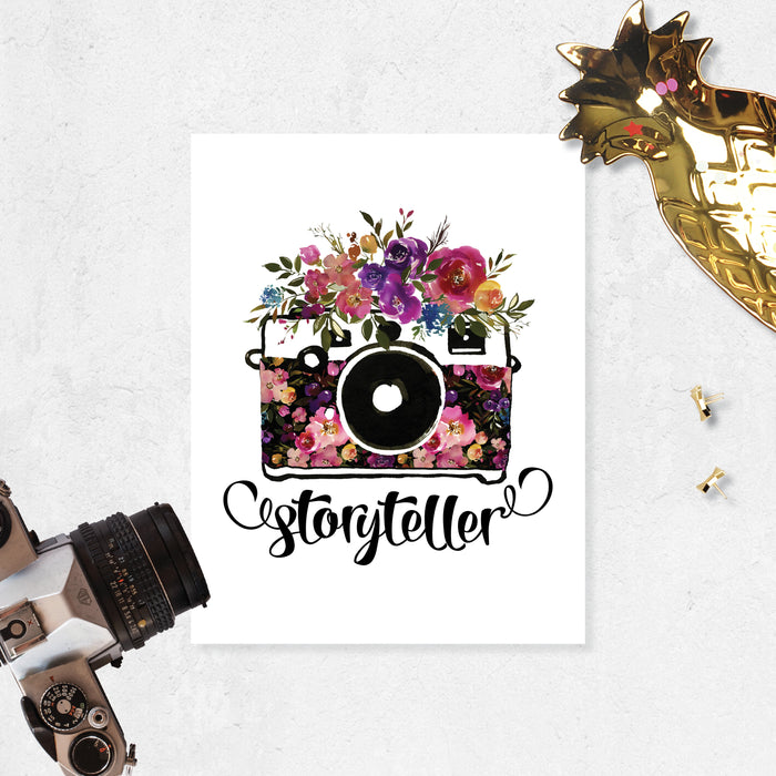 storyteller with watercolor camera and flowers in the body of the camera and on top in shades of pinks, purples, yellow, and blue with greenery printed on matte white paper