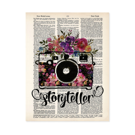 storyteller with watercolor camera and flowers in the body of the camera and on top in shades of pinks, purples, yellow, and blue with greenery printed on a dictionary page