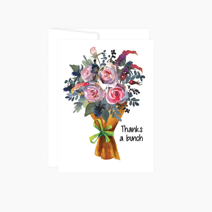 bouquet of watercolor flowers in pinks and blues wrapped in brown market paper tied with a green ribbon with the words thanks a bunch, this greeting card is blank inside