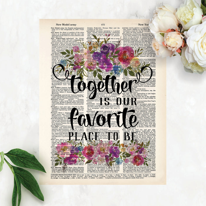 together is our favorite place to be with watercolor flowers in pinks, purples, blues with greenery top and bottom printed on a dictionary page