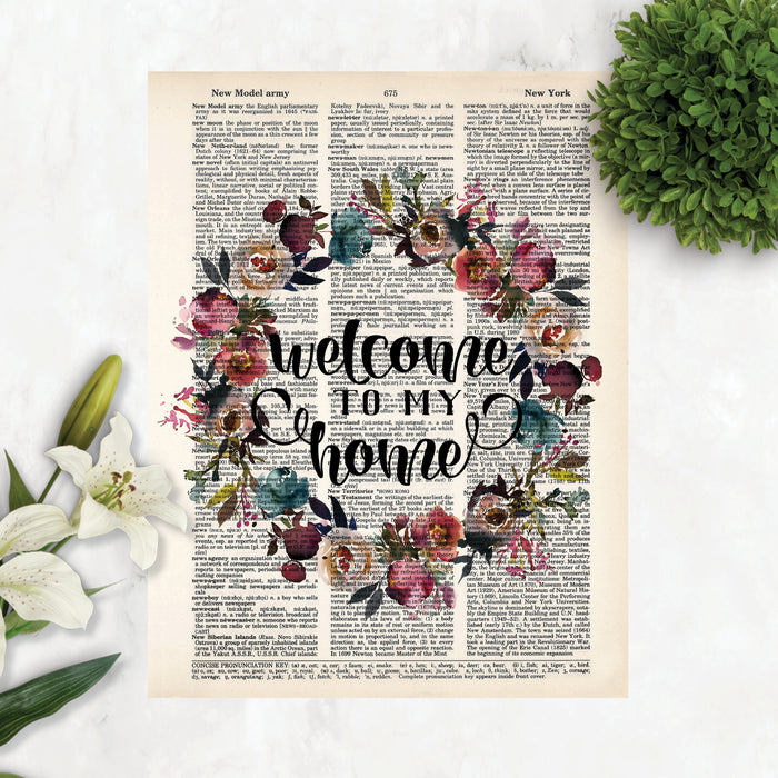 welcome to my home surrounded by a watercolor wreath in muted tones of pink, purple, blue and greenery printed on a dictionary page