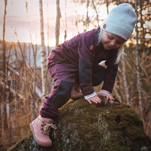 little girl climbing a rock wearing burgundy wool fleece set by Tufte