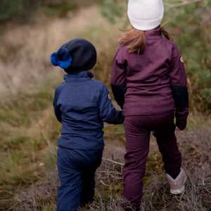 little boy and girl holding hands and walking away wearing tufte wool fleece set
