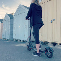 Lady riding by beach huts Xiaomi m365 electric scooter bought from Scooter Hub