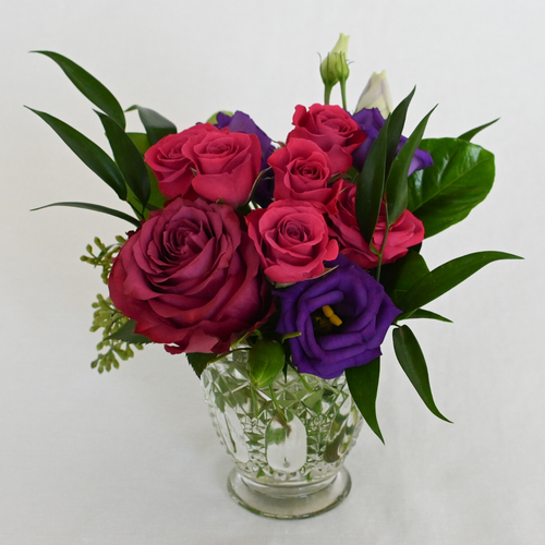 Red Fox Floral. Berry Accent Arrangement. A petite gathering of deep purple, berry, and hot pink flowers. Includes garden roses, spray roses, ranunculus, lisianthus, stock and with eucalyptus and green foliage.
