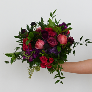 Red Fox Floral. Berry Bridal Bouquet. An organically designed, garden style bouquet made with a mix of deep purples, burgundies, and hot pink flowers such as garden roses, spray roses, ranunculus, lisianthus, stock and a mix green foliage.