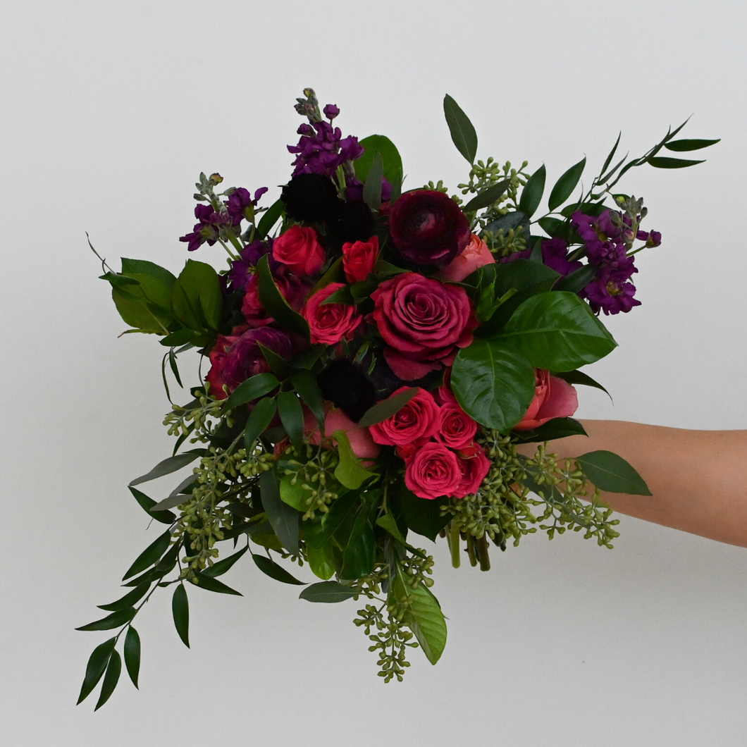 Red Fox Floral. Berry Bridesmaid Bouquet. An organically designed, garden style bouquet made with a mix of deep purples, burgundies, and hot pink flowers such as garden roses, spray roses, ranunculus, lisianthus, stock, and a mix of green foliage.