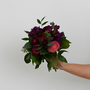 Red Fox Floral. Berry Nosegay. A petite, organically designed, garden style bouquet made with deep purples, burgundies, and hot pink flowers such as garden roses, spray roses, ranunculus, lisianthus, stock and a mix of green foliage.