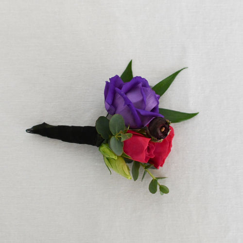 Red Fox Floral. Berry Boutonniere. A boutonniere made with a deep purple flower, hot pink and berry accents and a mix of green foliage.