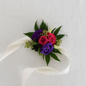 Red Fox Floral. Berry Corsage. A wrist corsage made with deep purple flowers and hot pink and berry accents and greens tied with white satin ribbon.