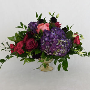 Red Fox Floral. Large Berry Centerpiece. A luxurious arrangement with picked from the garden texture made with a mix of deep purples, berry, and hot pink flowers. Includes garden roses, spray roses, ranunculus, lisianthus, stock, carnations, hydrangea with eucalyptus and green foliage.