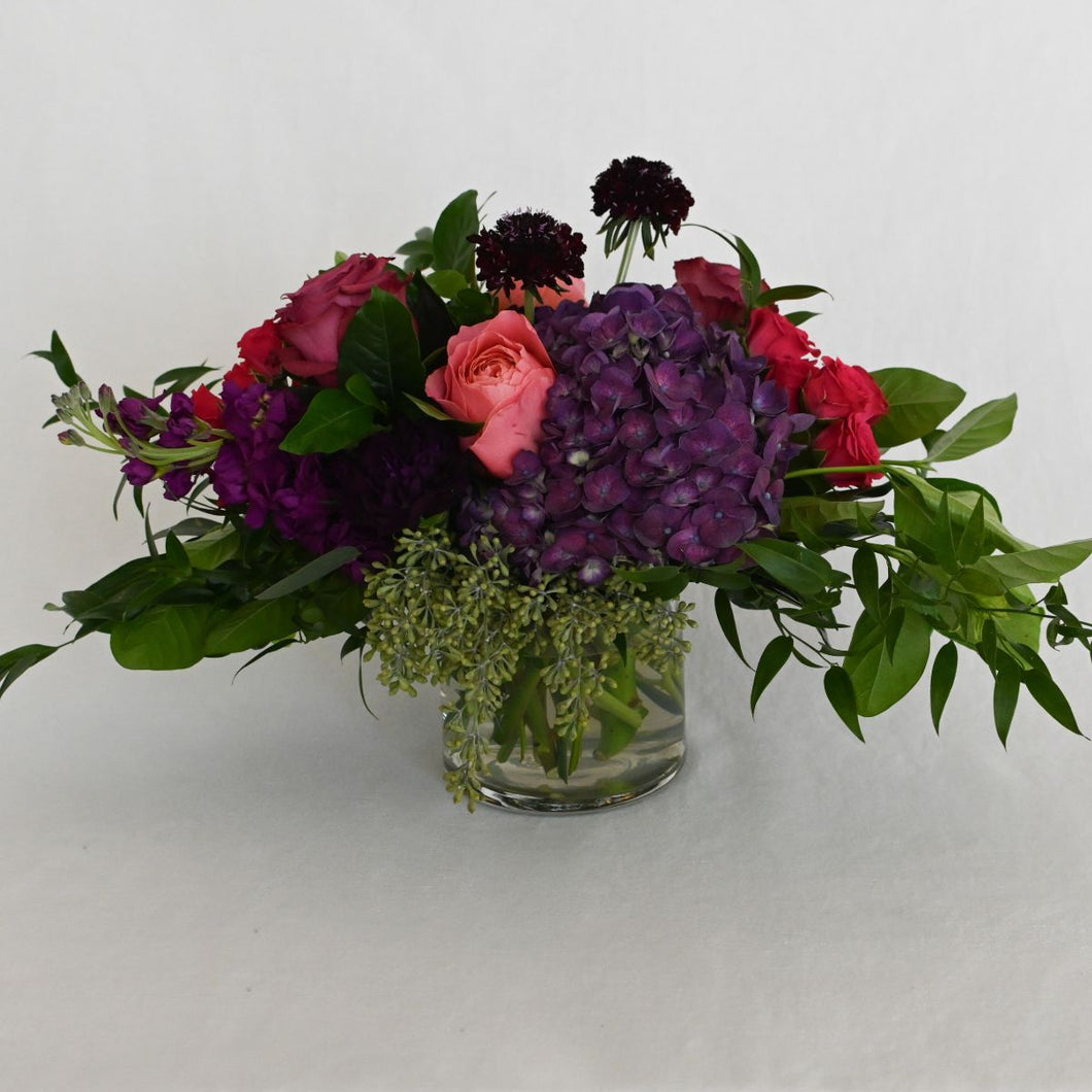 Red Fox Floral. Small Berry Centerpiece. A low and lush arrangement with picked from the garden texture made with a mix of deep purples, berry, and hot pink flowers. Includes garden roses, spray roses, ranunculus, lisianthus, carnations, stock, hydrangea with eucalyptus and green foliage.