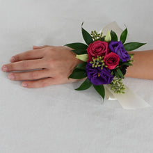 Load image into Gallery viewer, Red Fox Floral. Berry Corsage. A wrist corsage made with deep purple flowers and hot pink and berry accents and greens tied with white satin ribbon.