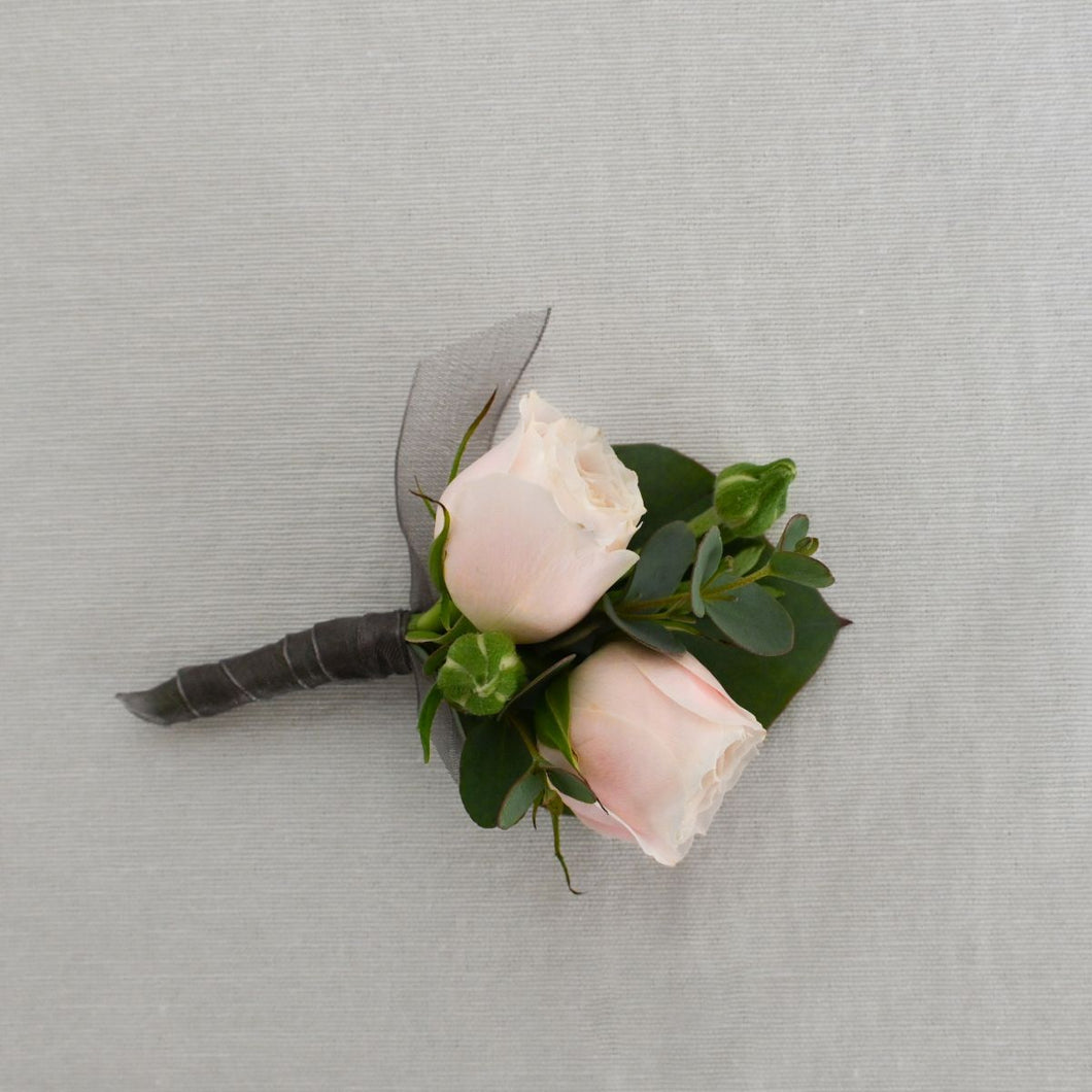 Red Fox Floral. Blush Boutonniere. A boutonniere made with a blush flower, white accents, and a mix of green foliage.