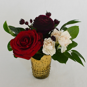 Red Fox Floral. Burgundy Accent Arrangement. A petite gathering of burgundy, dark red, and champagne garden roses, spray roses, ranunculus, dahlias and a mix of green foliage.