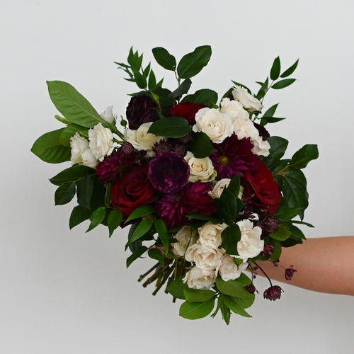 Red Fox Floral. Burgundy Bridal Bouquet. A lushly gathered bouquet made with dark red, burgundy, and champagne flowers such as garden roses, spray roses, ranunculus, dahlias, and a mix of green foliage.