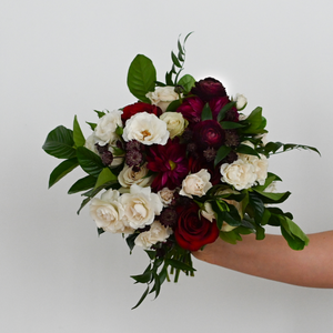 Red Fox Floral. Burgundy Bridesmaid Bouquet. A lushly gathered bouquet made with dark red, burgundy, and champagne flowers such as garden roses, spray roses, ranunculus, dahlias, and a mix of green foliage.