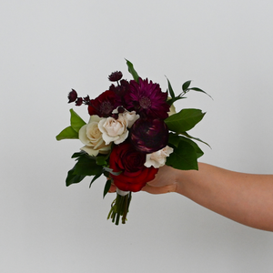Red Fox Floral. Burgundy Nosegay. A petite, lush nosegay made with dark red, burgundy, and champagne flowers such as garden roses, spray roses, ranunculus, dahlias, and a mix of green foliage.