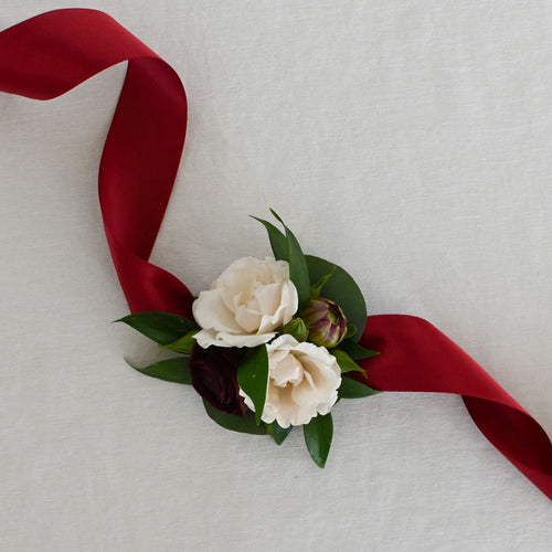 Red Fox Floral. Burgundy Corsage. A wrist corsage made with burgundy and champagne flowers with greens tied with burgundy satin ribbon.