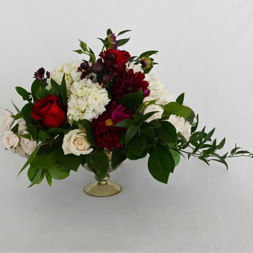 Red Fox Floral. Large Burgundy Centerpiece.  luxurious arrangement made with a mix of dark reds, burgundies, and champagne flowers. Includes garden roses, spray roses, ranunculus, hydrangea, dahlia with eucalyptus and green foliage.