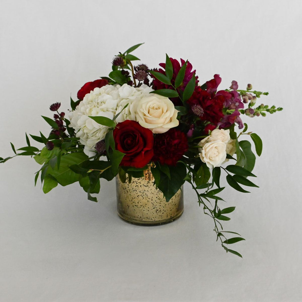 Red Fox Floral. Small Burgundy Centerpiece. A low and lush arrangement made with a mix of dark reds, burgundies and champagne flowers. Includes garden roses, spray roses, ranunculus, hydrangea, dahlias, and a mix of green foliage.