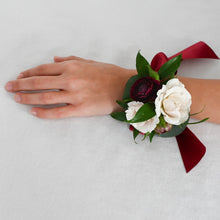 Load image into Gallery viewer, Red Fox Floral. Burgundy Corsage. A wrist corsage made with burgundy and champagne flowers with greens tied with burgundy satin ribbon.
