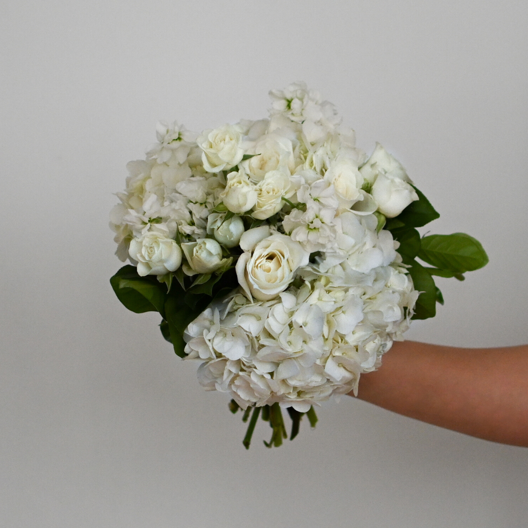 Red Fox Floral Classic Elegance Bridesmaid Bouquet. A traditional rounded bouquet made with classic white flowers such as hydrangea, roses, spray roses, and stock with hints of green foliage.