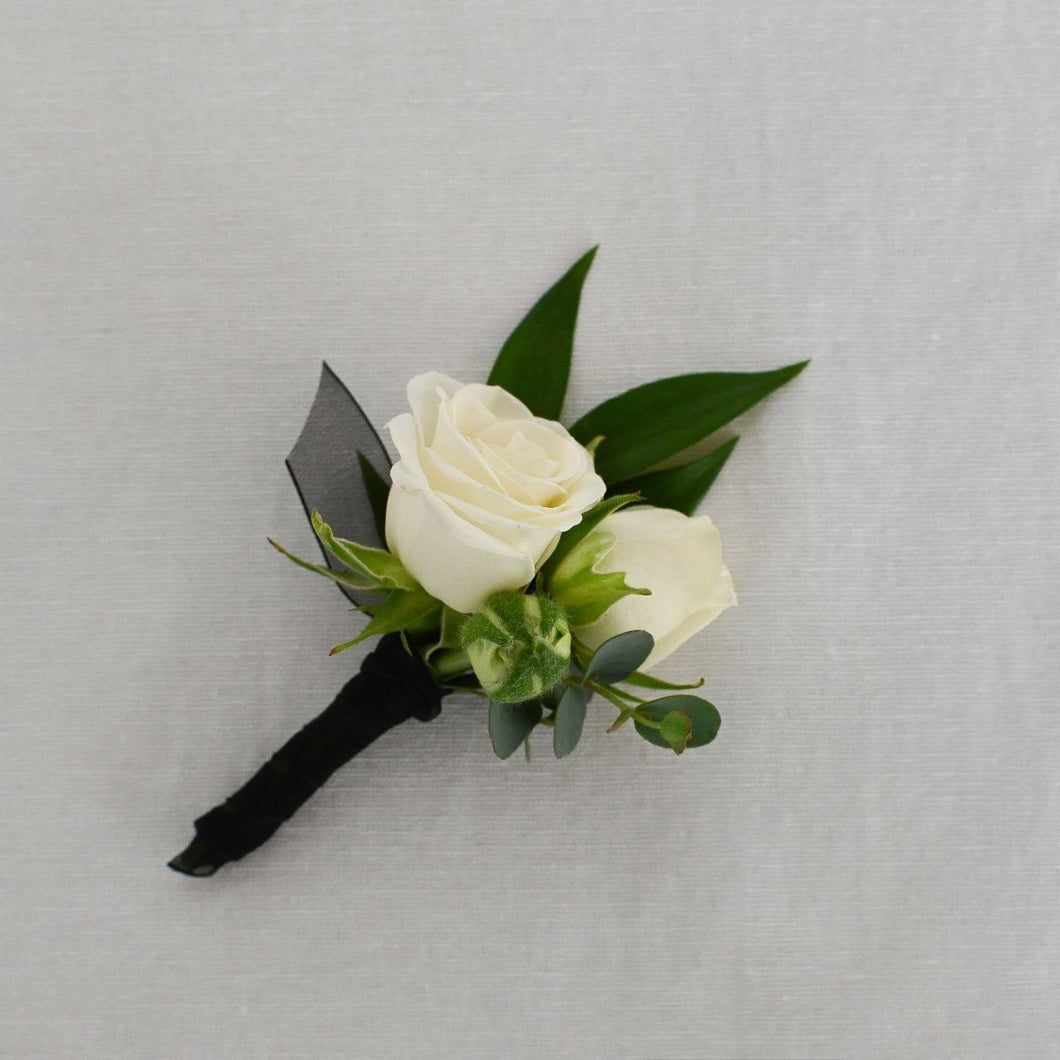 Red Fox Floral. Classic Elegance Boutonniere. A boutonniere made with white spray roses and green accents.  Stems will be wrapped in black ribbon.