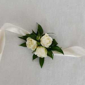 Red Fox Floral Classic Elegance Corsage. A wrist corsage made with White spray roses and accent greens tied with white satin ribbon.