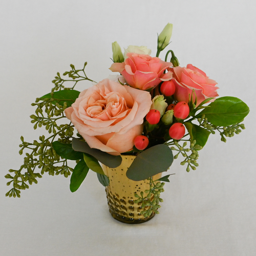 Red Fox Floral Coral Accent Arrangement. A petite gathering of coral and peach garden roses, spray roses, ranunculus, and berry accents with eucalyptus and green foliage.