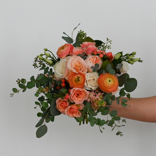 Red Fox Floral Coral Bridal Bouquet. A lavish, rounded style bouquet made with bright peach, coral, and ivory flowers such as garden roses, spray roses, ranunculus, lisianthus, and berry accents and a mix of eucalyptus and green foliage.