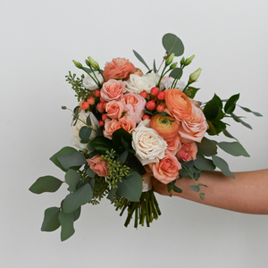 Red Fox Floral Coral Bridesmaid Bouquet. A lavish, rounded style bouquet made with bright peach, coral, and ivory flowers such as garden roses, spray roses, ranunculus, lisianthus, berry accents, and a mix of eucalyptus and green foliage.