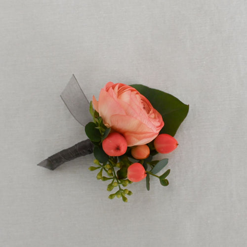 Red Fox Floral Coral Boutonniere. A boutonniere made with a coral flower and accents, and a mix of green foliage.