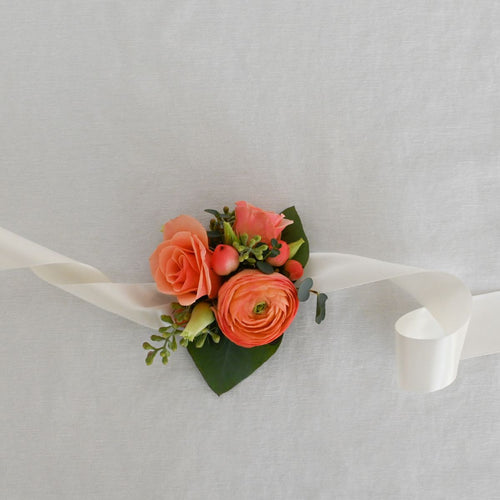 Red Fox Floral Coral Corsage. A wrist corsage made with coral and peach flowers and ivory accents and greens tied with white satin ribbon.