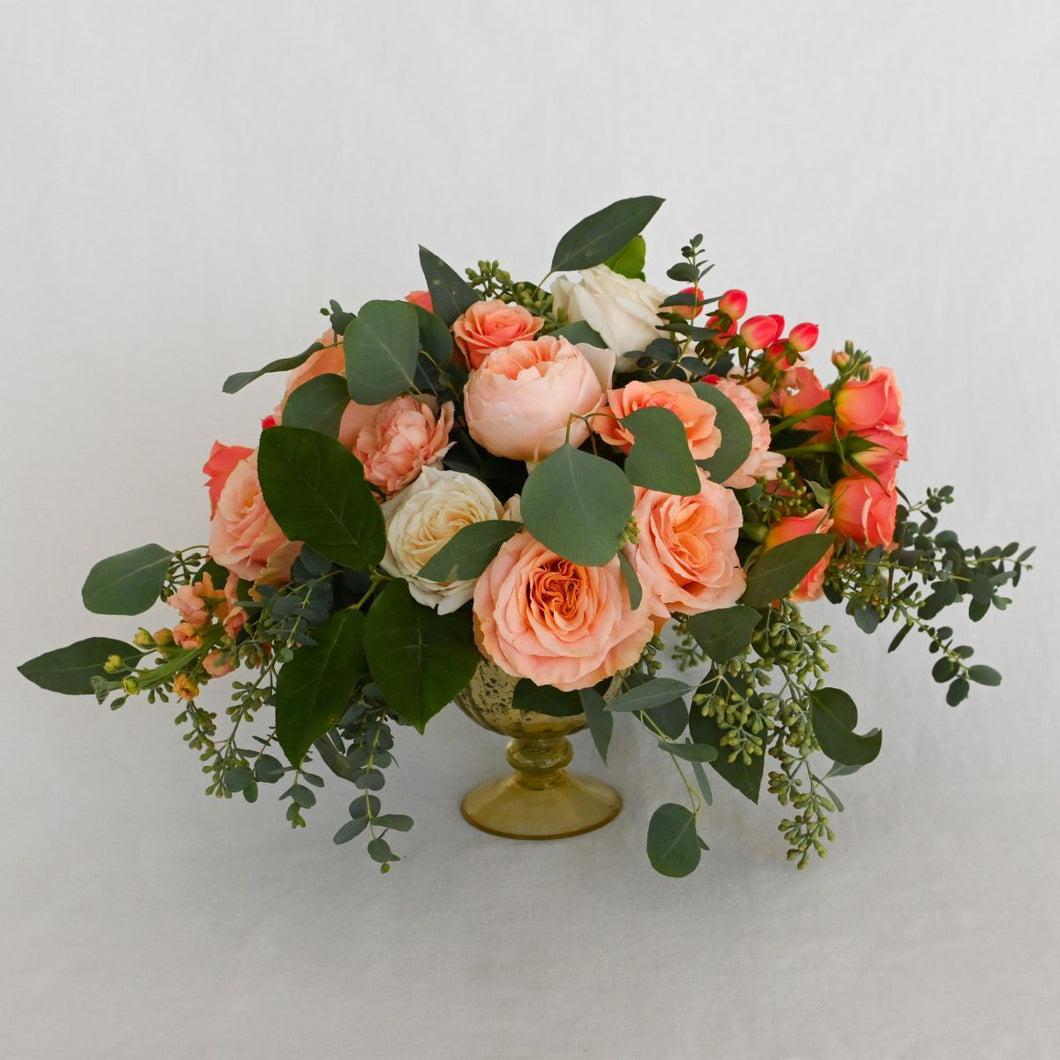 Red Fox Floral Large Coral Centerpiece. A lavish arrangement with picked from the garden texture made with coral, peach and ivory garden roses, spray roses, ranunculus, lisianthus, berry accents with eucalyptus and green foliage.