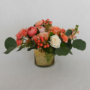 Red Fox Floral Small Coral Centerpiece. A low and lavish arrangement with picked from the garden texture made with coral, peach and ivory garden roses, spray roses, ranunculus, lisianthus, and berry accents with eucalyptus and green foliage.