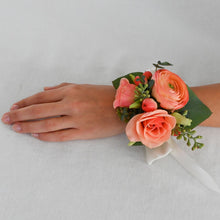 Load image into Gallery viewer, Red Fox Floral Coral Corsage. A wrist corsage made with coral and peach flowers and ivory accents and greens tied with white satin ribbon.