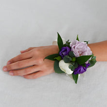 Load image into Gallery viewer, Red Fox Floral Purple Corsage. A wrist corsage made with purple and lavender flowers with white accents and greens tied with white satin ribbon.