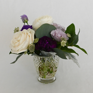 Red Fox Floral Purple Accent Arrangement. A petite gathering of purple, lavender, and white garden roses, spray roses, ranunculus, lisianthus, stock and with eucalyptus and green foliage.