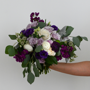 Red Fox Floral Purple Bridal Bouquet. An organically designed, garden style bouquet made with dark purple, lavender, and white flowers such as garden roses, spray roses, ranunculus, lisianthus, stock and a mix of eucalyptus and green foliage.