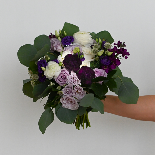 Red Fox Floral Purple Bridesmaid Bouquet. An organically designed, garden style bouquet made with purple, lavender, and white flowers such as garden roses, spray roses, ranunculus, lisianthus, stock, and a mix of eucalyptus and green foliage.