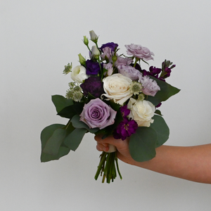 Red Fox Floral Purple Nosegay. A petite, organically designed, garden style bouquet made with purple, lavender, and white flowers such as garden roses, spray roses, ranunculus, lisianthus, stock and a mix of eucalyptus and green foliage.